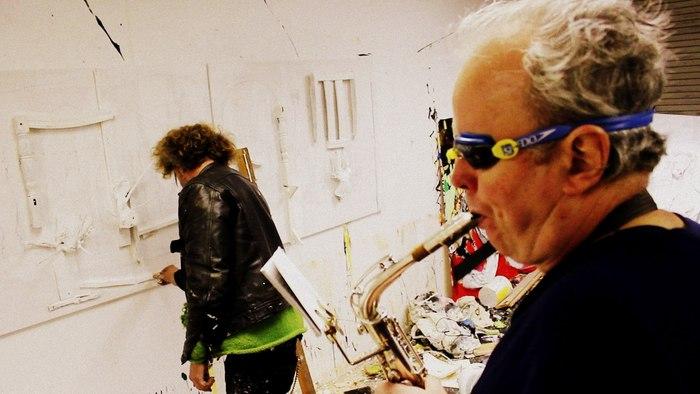 Mark Summers plays saxophone while Jonny paints